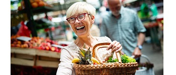 Senior woman buying fresh vegetables and fruits at the local market